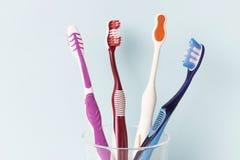 Cepillos de dientes multicolores en una taza de cristal, fondo azul fotos de archivo