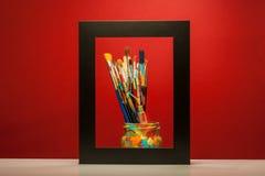 Cepillos de pintura de los artes en marco con el fondo rojo Fotografía de archivo libre de regalías