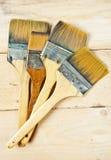 Cepillos de pintura viejos en fondo de madera Imágenes de archivo libres de regalías
