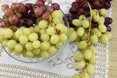 Cepillos de uvas frescas de diferentes tipos en un platillo hermoso Imagen de archivo
