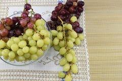Cepillos de uvas frescas de diferentes tipos en un platillo hermoso Imagen de archivo libre de regalías