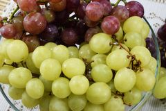 Cepillos de uvas frescas de diferentes tipos en un platillo hermoso Foto de archivo libre de regalías