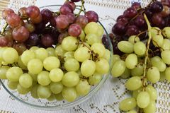 Cepillos de uvas frescas de diferentes tipos en un platillo hermoso Fotos de archivo libres de regalías