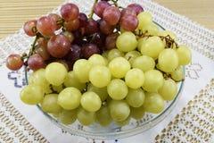 Cepillos de uvas frescas de diferentes tipos en un platillo hermoso Fotografía de archivo