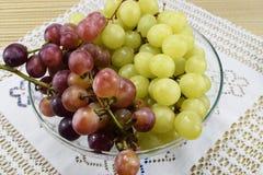 Cepillos de uvas frescas de diferentes tipos en un platillo hermoso Fotos de archivo