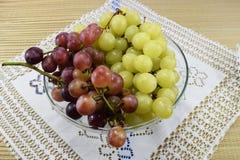 Cepillos de uvas frescas de diferentes tipos en un platillo hermoso Imagenes de archivo