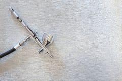 Cepillos del aerógrafo y del arte en un fondo de plata Imagen de archivo libre de regalías