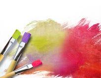 Cepillos del artista con una lona a medio terminar Imágenes de archivo libres de regalías