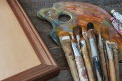 Cepillos del artista, de la pintura y de la lona en el marco imagen de archivo libre de regalías