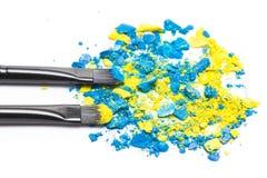 Cepillos del maquillaje con sombreador de ojos azul y amarillo compacto machacado Imagenes de archivo