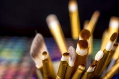Cepillos del maquillaje delante de las paletas del maquillaje Fotos de archivo libres de regalías