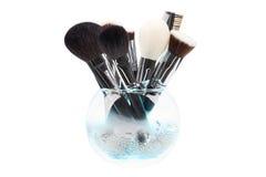 Cepillos del maquillaje en el florero de cristal cristales Humo azul Aislado Wh Foto de archivo libre de regalías