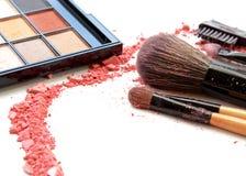 cepillos del maquillaje en el tenedor y los cosméticos aislados en blanco foto de archivo