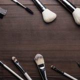 Cepillos del maquillaje en fondo de madera Imagenes de archivo