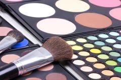 Cepillos del maquillaje en las gamas de colores de los sombreadores de ojos Foto de archivo