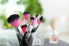 Cepillos del maquillaje en tenedor en fondo Imagen de archivo