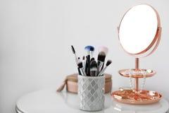 Cepillos del maquillaje en tenedor en la tabla Imágenes de archivo libres de regalías