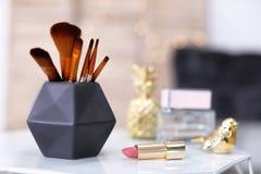 Cepillos del maquillaje en tenedor y lápiz labial Fotos de archivo libres de regalías