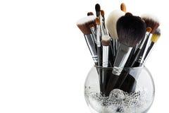 Cepillos del maquillaje en un florero de cristal Imágenes de archivo libres de regalías
