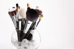 Cepillos del maquillaje en un florero de cristal con los cristales Fotos de archivo libres de regalías