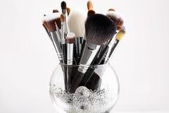 Cepillos del maquillaje en un florero de cristal con los cristales Imagenes de archivo