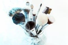 Cepillos del maquillaje en un florero de cristal Humo azul Fotografía de archivo