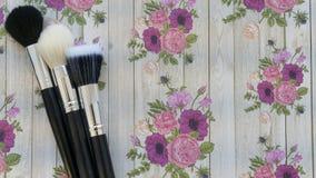 Cepillos del maquillaje en un fondo floral fotos de archivo