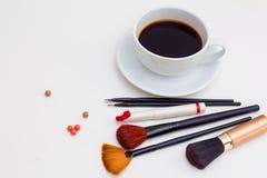 Cepillos del maquillaje, lápiz labial, taza de café imagen de archivo