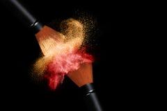 Cepillos del maquillaje que aplican el polvo aislado en negro Foto de archivo