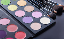 Cepillos del maquillaje y sombras de ojos del maquillaje en el escritorio Imagenes de archivo