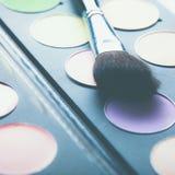 Cepillos del maquillaje y sombras de ojos del maquillaje en el escritorio Fotos de archivo