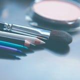 Cepillos del maquillaje y sombras de ojos del maquillaje en el escritorio Fotografía de archivo libre de regalías