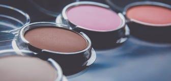 Cepillos del maquillaje y sombras de ojos del maquillaje en el escritorio Foto de archivo libre de regalías