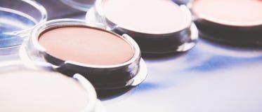 Cepillos del maquillaje y sombras de ojos del maquillaje en el escritorio Fotografía de archivo