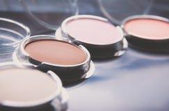 Cepillos del maquillaje y sombras de ojos del maquillaje en el escritorio Imagen de archivo libre de regalías