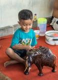 Cepillos del muchacho en el negocio de Sari Pertiwi Wood Carving, Juga, Bali, Indonesia foto de archivo