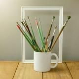 Cepillos del pintor en la taza blanca en la tabla de madera Taza para la mofa de la exhibición del logotipo para arriba Fotografía de archivo