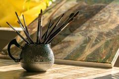 Cepillos del pintor en un jarro en la tabla imagen de archivo