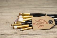 Cepillos felices de la etiqueta y del maquillaje del día del ` s de las mujeres Foto de archivo libre de regalías
