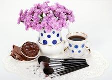 Cepillos, flores y taza del maquillaje de café con la magdalena Imágenes de archivo libres de regalías