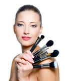 Cepillos hermosos del maquillaje de la explotación agrícola de la mujer joven Imagen de archivo