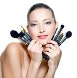 Cepillos hermosos del maquillaje de la explotación agrícola de la mujer joven Foto de archivo