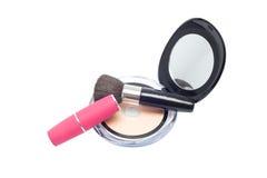 Cepillos, lápiz labial rosado y polvo con el espejo Imagen de archivo libre de regalías