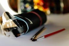 Cepillos, pinturas y papel de dibujo en un fondo blanco, conceptual para los artistas y los dise?adores libre illustration