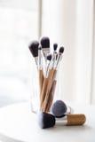 Cepillos profesionales del maquillaje en un vidrio Fotografía de archivo