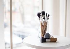Cepillos profesionales del maquillaje en un vidrio Fotos de archivo