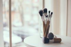 Cepillos profesionales del maquillaje en un vidrio Imágenes de archivo libres de regalías
