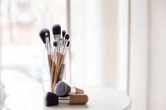 Cepillos profesionales del maquillaje en un vidrio Foto de archivo