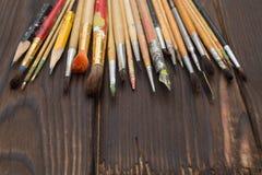 Cepillos separados hacia fuera en una superficie de madera oscura Foto de archivo