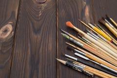 Cepillos separados hacia fuera en una superficie de madera oscura Fotos de archivo libres de regalías